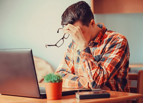 Tired young man sitting over laptop in the office